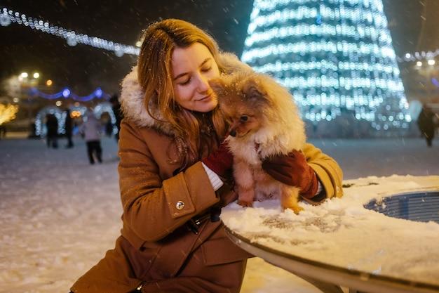 Wizerunek młodej uroczej dziewczyny z psem, pomorskim, plenerowym, pod śniegiem. dziewczyna przytula swojego psa na ulicy w zimie. zimowy czas