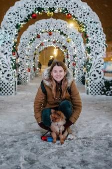 Wizerunek młodej uroczej dziewczyny z psem, pomorskim, plenerowym, pod śniegiem. zimowy czas