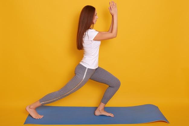 Wizerunek młody piękny kobiety joga pozować isalated nad żółtym studiiem