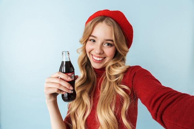 Wizerunek modnej blond kobieta 20s ubrana w czerwony beret trzymając szklaną butelkę z sodą podczas robienia zdjęcia selfie na białym tle