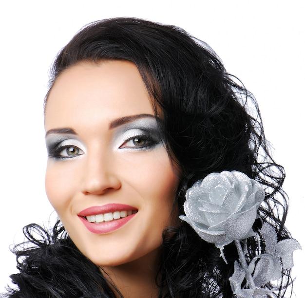 Wizerunek mody. piękna uśmiechnięta kobieta z streszczenie srebrną różą.