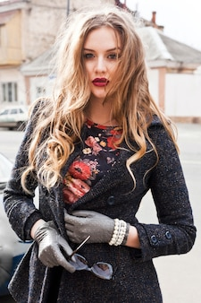 Wizerunek mody plenerowej pięknej eleganckiej kobiety z długimi kręconymi blond włosami i dużymi, jasnymi, pełnymi ustami pozuje na ulicy w eleganckim ciepłym płaszczu. jesienny portret.