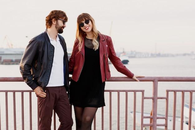 Wizerunek mody zewnętrznej stylowej pary w swobodnym stroju, skórzanej kurtce i okularach przeciwsłonecznych stojących na moście. przystojny mężczyzna z brodą ze swoją dziewczyną spędzający razem romantyczny czas.