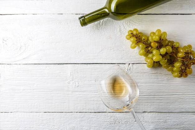 Wizerunek na kieliszek do wina z winem, winogronami, butelka na białym drewnianym stole