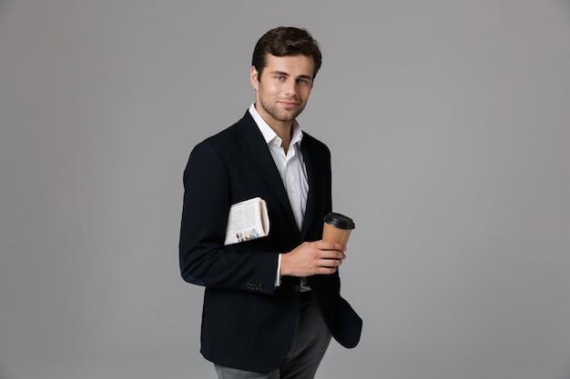 Wizerunek nieogolonego mężczyzny 30s w garniturze, trzymającego kawę i gazetę, na białym tle nad szarą ścianą