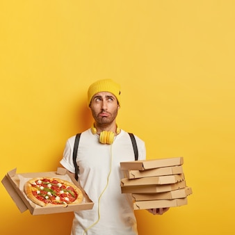 Wizerunek niezadowolonego dostawczyni trzyma stos kartonów, pokazuje smaczną pizzę z serem, ma smutny wyraz twarzy, nosi żółty kapelusz i białą koszulkę