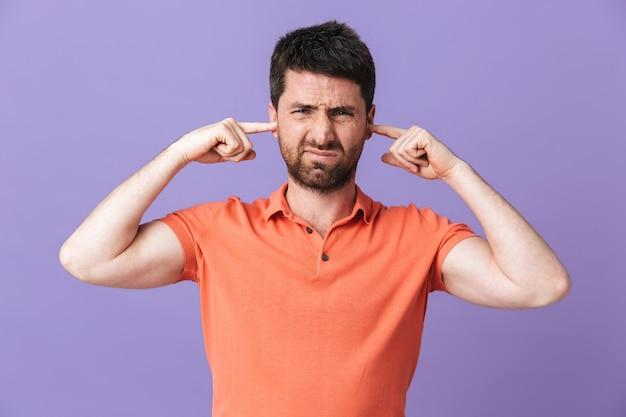 Wizerunek niezadowolony młody przystojny brodaty mężczyzna pozowanie na białym tle nad fioletowe ściany pokrywające uszy.