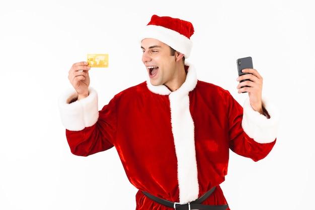 Wizerunek optymistycznego mężczyzny lat 30. w stroju świętego mikołaja trzymającego telefon komórkowy i kartę kredytową
