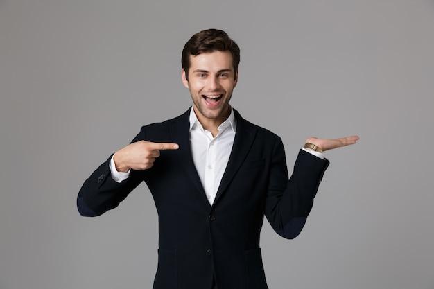Wizerunek optymistyczny biznesmen 30s w formalnym garniturze, wskazując palcami na bok na copyspace na dłoni, odizolowane na szarej ścianie