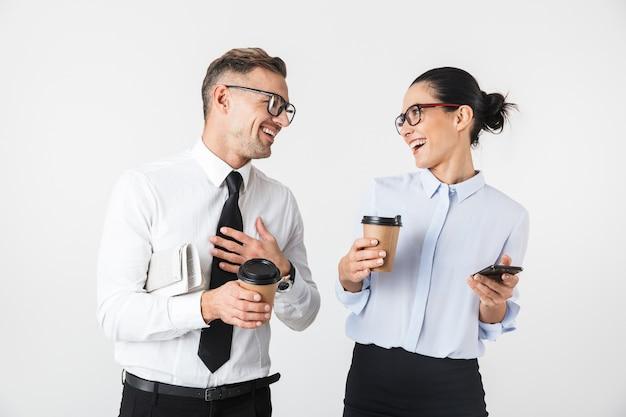 Wizerunek pary młodych współpracowników biznesowych samodzielnie nad białą ścianą picia kawy przy użyciu telefonów komórkowych.