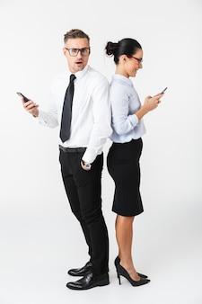 Wizerunek pary młodych współpracowników biznesowych za pomocą telefonów komórkowych izolowanych na białej ścianie.