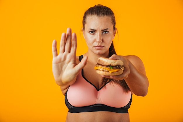 Wizerunek pewnej kobiety z nadwagą w dresie robi gest stopu trzymając kanapkę, odizolowane na żółtym tle