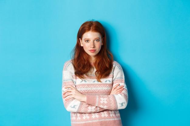 Wizerunek pewnej siebie nastolatki z rudymi włosami patrząc odważnie w kamerę, skrzyżowanymi rękami na piersi i wpatrującą się w kamerę, stojącą w zimowym swetrze na niebieskim tle.