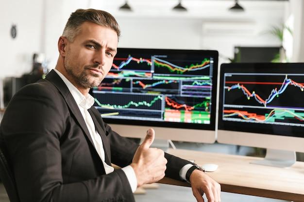 Wizerunek pewność biznesmen 30s ubrany w garnitur pracujący w biurze na komputerze z grafiką i wykresami na ekranie