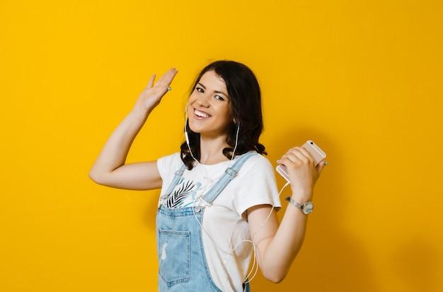 Wizerunek piękna azjatykcia szczęśliwa dziewczyna słucha muzyka w hełmofonach i tanczy nad kolor żółty ścianą