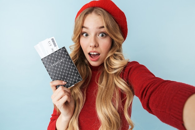 Wizerunek piękna blond kobieta 20s ubrana w czerwony beret, trzymając paszport i bilet podróżny podczas robienia zdjęcia selfie na białym tle