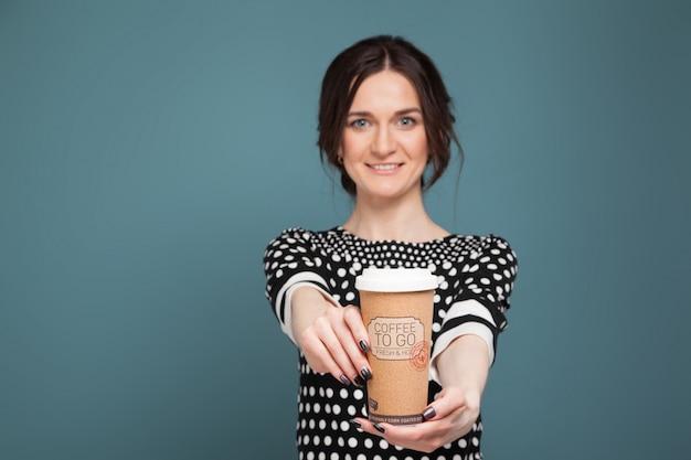 Wizerunek piękna kobieta w cętkowanym odzieżowym pozyci z kawą w rękach