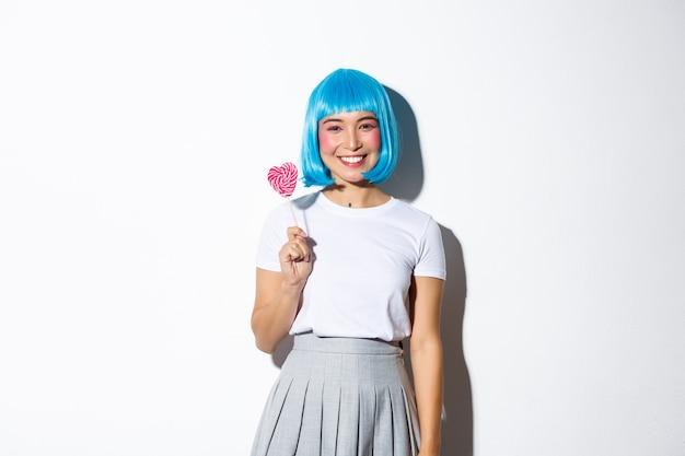Wizerunek pięknej azjatyckiej dziewczyny w niebieskiej krótkiej peruce z okazji halloween, trzymając cukierki i uśmiechając się do kamery, stojąc.