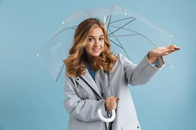 Wizerunek pięknej blond kobiety 20s ubrana w płaszcz przeciwdeszczowy stojącej pod przezroczystym parasolem