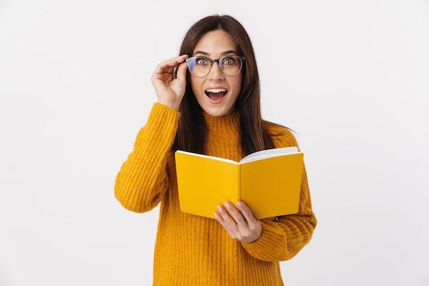 Wizerunek pięknej brunetki dorosłej kobiety noszącej okulary robiącej notatki w pamiętniku na białym tle