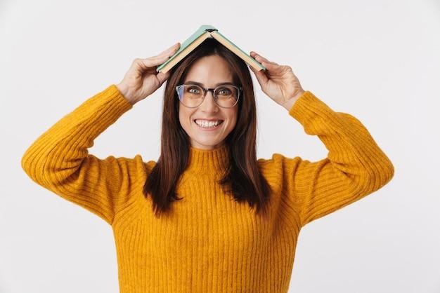 Wizerunek pięknej brunetki dorosłej kobiety w okularach, uśmiechniętej i trzymającej książkę przy głowie na białym tle