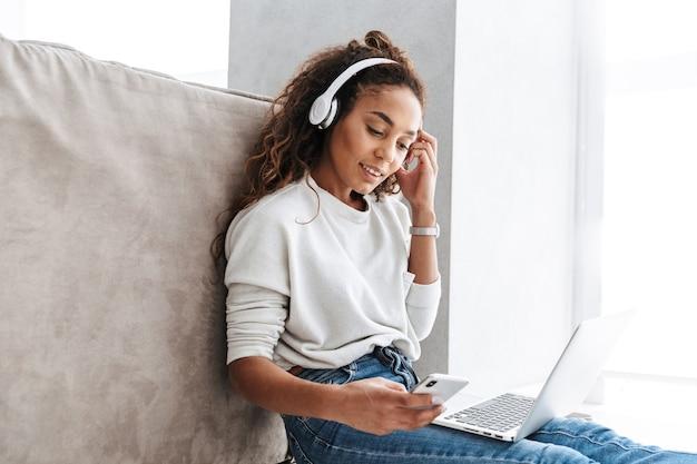 Wizerunek pięknej dziewczyny african american na sobie słuchawki za pomocą laptopa i smartfona, siedząc na podłodze w jasnym salonie