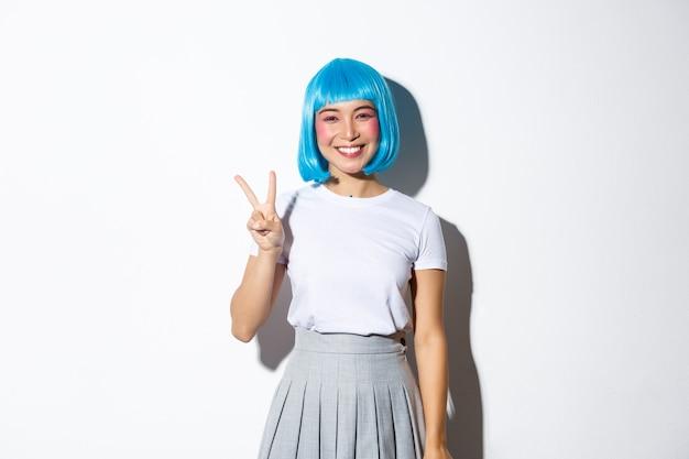 Wizerunek pięknej dziewczyny anime w niebieskiej peruce pokazujący gest pokoju. kobieta ubrana w strój na halloween, uśmiechnięta szczęśliwa i stojąca.