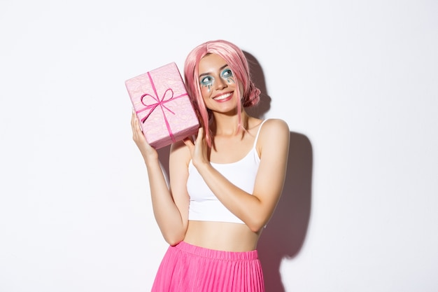 Wizerunek pięknej dziewczyny w różowej peruce potrząsając pudełkiem z prezentem urodzinowym, zastanawiam się, co jest w zapakowanym pudełku, stojąc.