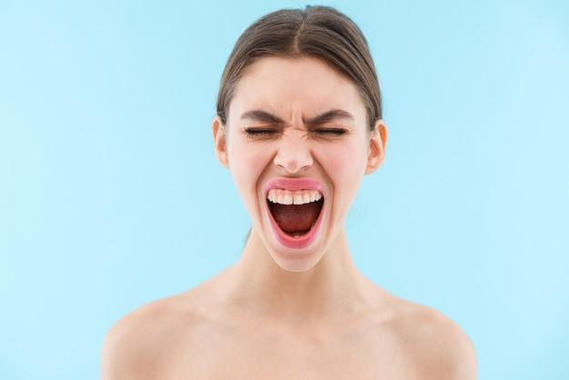 Wizerunek pięknej, emocjonalnej krzyczącej młodej kobiety, pozowanie na białym tle.