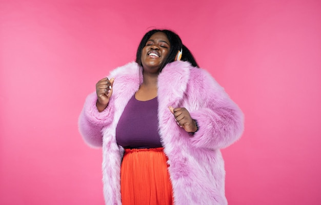 Wizerunek pięknej kobiety pozującej w futrzanym płaszczu na różowym tle
