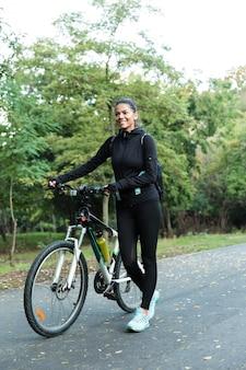 Wizerunek pięknej kobiety spaceru na rowerze w parku na świeżym powietrzu.