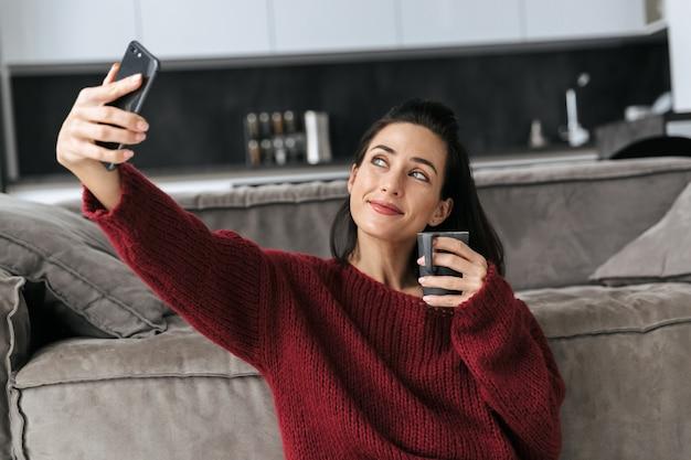Wizerunek pięknej kobiety w domu w domu, w pobliżu sofy, zrób selfie przez telefon komórkowy pijąc kawę.