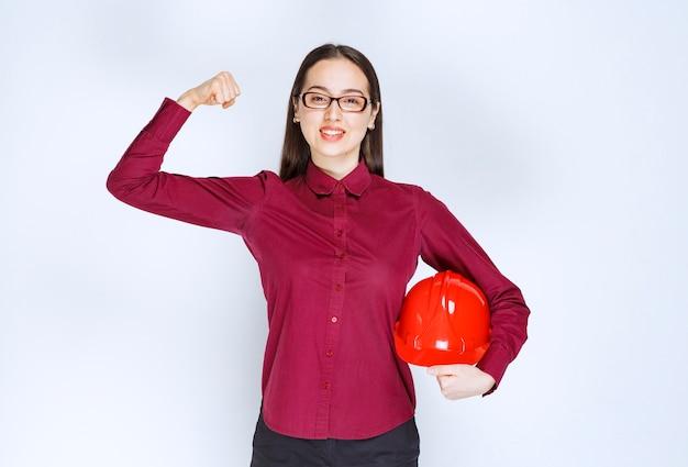 Wizerunek pięknej kobiety w okularach trzymającej kask i pokazujący mięśnie.