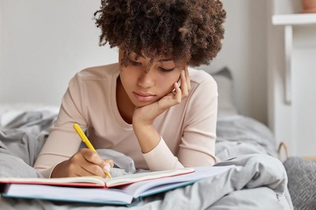 Wizerunek pięknej kobiety z fryzurą afro przepisuje informacje w notatniku z książki