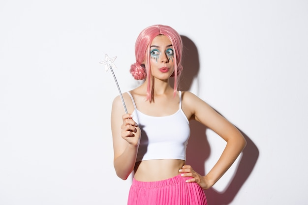 Wizerunek pięknej kobiety z różową peruką i jasnym makijażem, trzymającej magiczną różdżkę, wróżkę cosplay na przyjęcie z okazji halloween, stojącą.