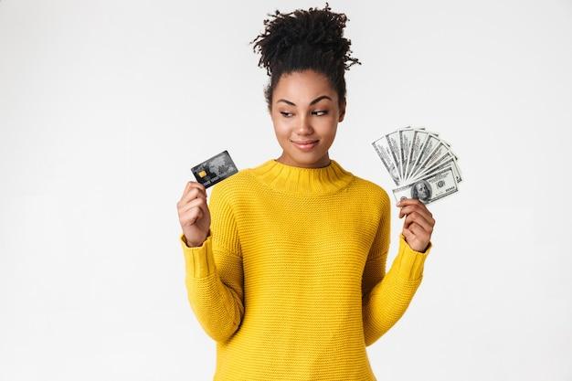 Wizerunek pięknej młodej afrykańskiej kobiety myślenia pozowanie na białej ścianie, trzymając pieniądze i kartę kredytową.