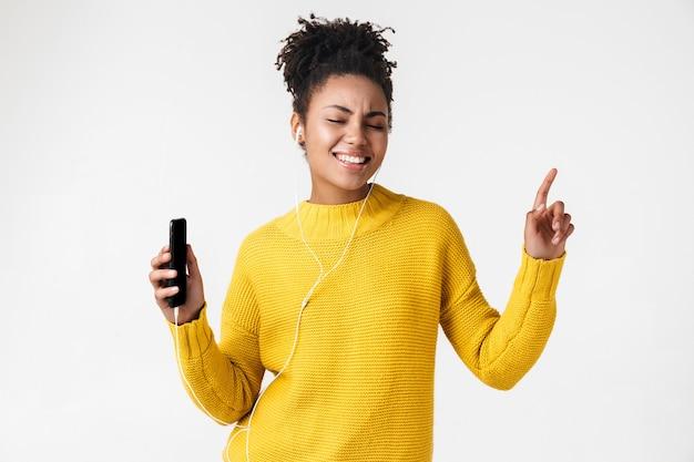 Wizerunek pięknej młodej afrykańskiej podekscytowanej emocjonalnej kobiety szczęśliwy pozowanie na białej ścianie słuchania muzyki ze słuchawkami za pomocą telefonu komórkowego.