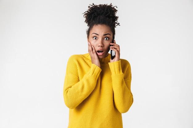 Wizerunek pięknej młodej afrykańskiej podekscytowany emocjonalny wstrząśnięty kobiety pozowanie na białej ścianie rozmawia przez telefon komórkowy.