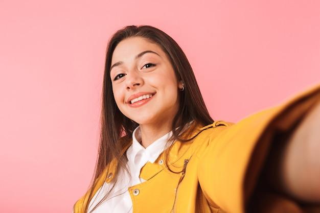 Wizerunek pięknej młodej dziewczyny pozowanie na białym tle nad różową ścianą weź selfie