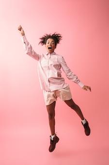 Wizerunek pięknej młodej kobiety afrykańskiej pozowanie na białym tle skoki.
