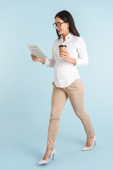 Wizerunek pięknej młodej kobiety biznesu na białym tle czytania gazety picia kawy.