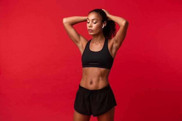 Wizerunek pięknej młodej kobiety fitness afrykańskiego sportu pozowanie na białym tle na czerwonej ścianie ściany słuchanie muzyki ze słuchawkami.