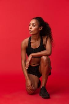 Wizerunek pięknej młodej kobiety fitness afrykańskiego sportu pozowanie na białym tle nad czerwoną ścianą.