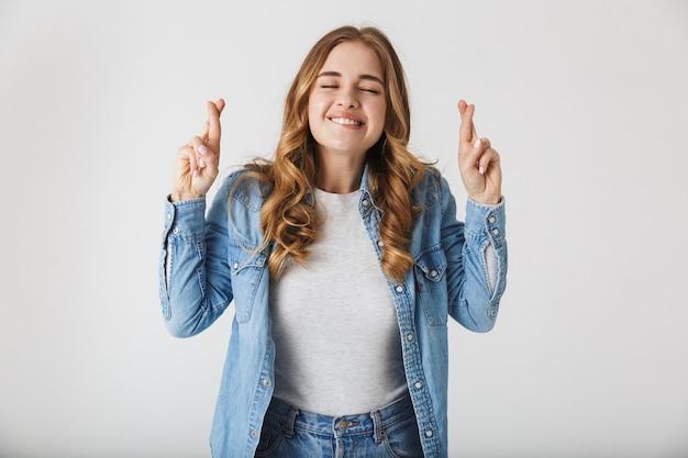 Wizerunek pięknej młodej kobiety ładnej pozowanie na białym tle nad białą ścianą sprawiają, że pełen nadziei proszę gest kciuki.