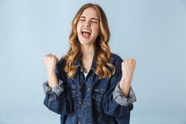 Wizerunek pięknej młodej kobiety ładnej pozowanie na białym tle nad niebieską ścianą zrobić kciuki gest zwycięzcy.