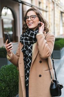 Wizerunek pięknej młodej kobiety na zewnątrz spaceru ulicą przy użyciu rozmowy przez telefon komórkowy słuchania muzyki przez słuchawki.