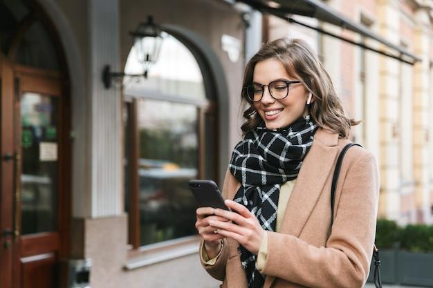 Wizerunek pięknej młodej kobiety na zewnątrz spaceru ulicą przy użyciu telefonu komórkowego słuchania muzyki przez słuchawki.