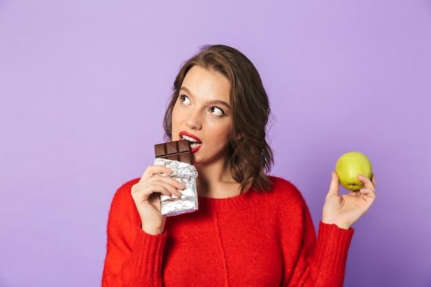 Wizerunek pięknej młodej kobiety pozowanie na białym tle nad fioletową ścianą, trzymając czekoladę i jabłko.