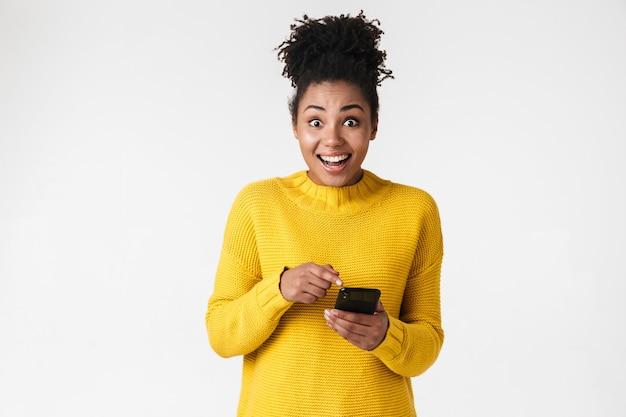 Wizerunek pięknej młodej kobiety szczęśliwy afryki pozowanie na białej ścianie za pomocą telefonu komórkowego.