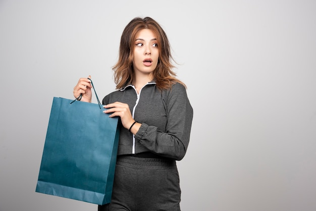 Wizerunek pięknej młodej kobiety trzymającej niebieską torbę sklepową.